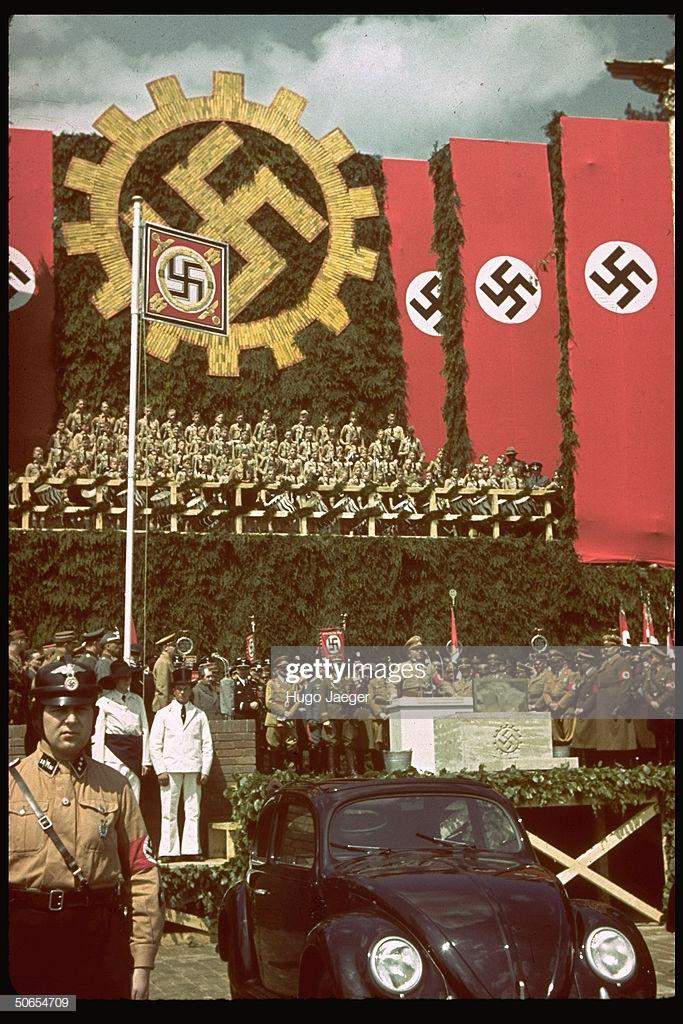 上图:1938年6月25日,希特勒在沃尔夫斯堡参加大众汽车厂的奠基仪式,前面是一辆大众甲壳虫汽车。希特勒上台后不久,就要求生产一种普通德国人买得起的「人民汽车」,可容纳2名成人和3名儿童、最高时速可达100km/h、最好采用风冷发动机,只卖990马克。奥地利工程师费迪南德·保时捷根据这一要求设计出著名的大众甲壳虫汽车。1936年10月12日,三辆大众VW-1下线。1938年,大众汽车公司在沃尔夫斯堡建厂,计划年产150万辆。二战期间,大众的生产能力被用于军备生产。