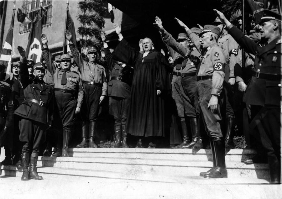 上图:1933年9月,路德维希·穆勒(Ludwig Müller)在威登堡召开的德国全国宗教大会上行纳粹礼。穆勒毕业于敬虔主义福音派高中,在哈勒大学(Halle)学习神学,一战时担任海军随军牧师,1931年加入纳粹党。1933年1月希特勒上台之后,德意志基督徒(German Christians)在德意志福音教会联合会(German Evangelical Church Confederation)的一些成员教会中掌权,同年4月将改组织改名为德意志福音教会(German Evangelical Church),成为受纳粹党领导的帝国教会(Protestant Reich Church)。同年9月,穆勒被选为帝国主教。从此德意志福音教会成为纳粹的跟班,战后被解散,由德国福音教会(Evangelical Church in Germany)取代。